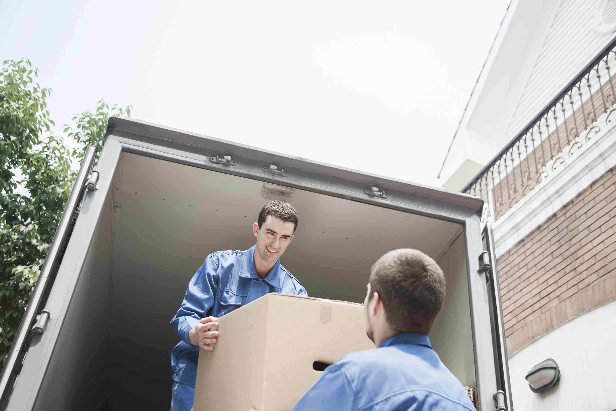 removalist men loading box onto truck