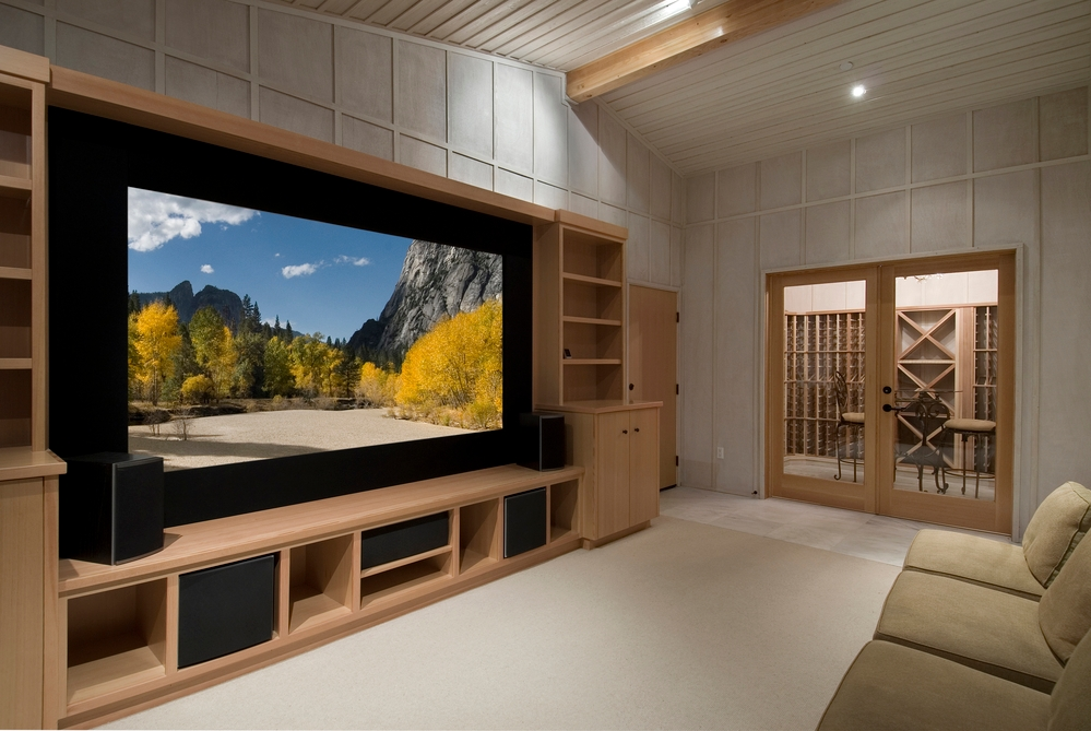 home theatre with wine tasting room, big screen, wood cabinets, photo on screen a shot from yosemite