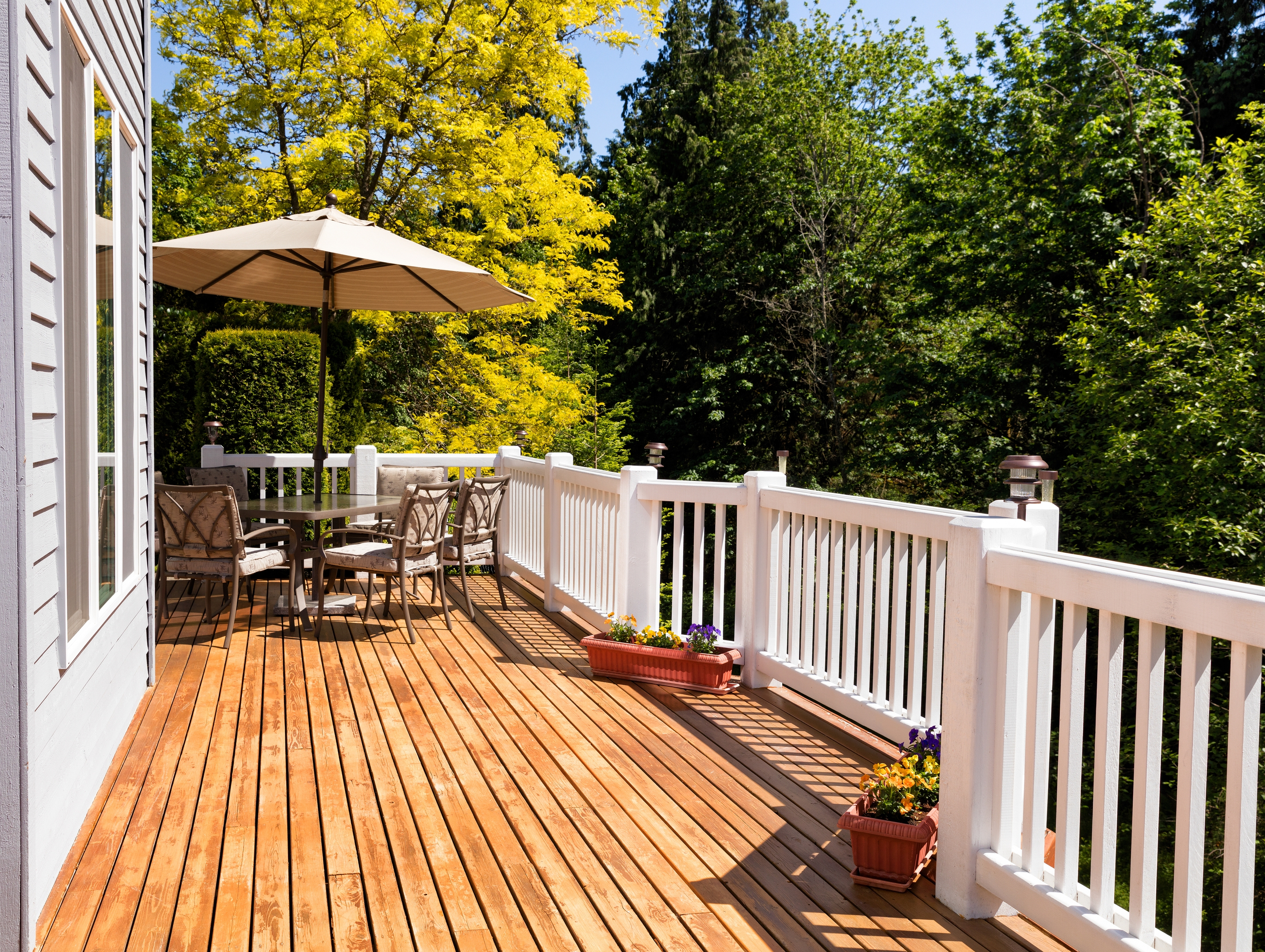 home outdoor cedar deck with furniture and open umbrella during nice bright day
