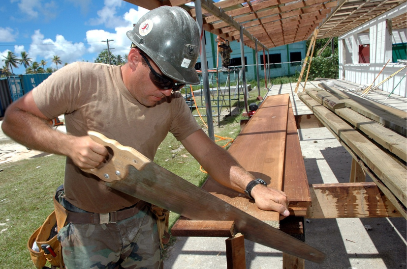 man with hardhat sawing wood outdoors