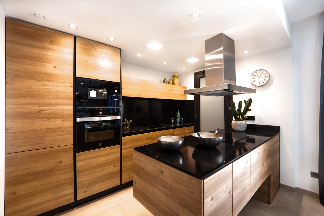 kitchen with black counter wood panels white walls