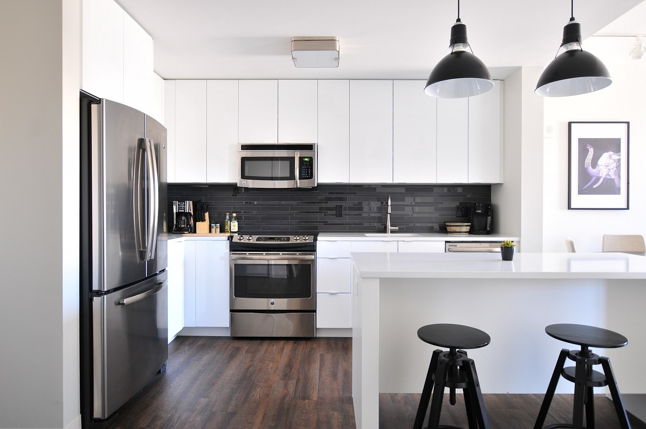 white kitchen counter cabinets walls with black stools and lights