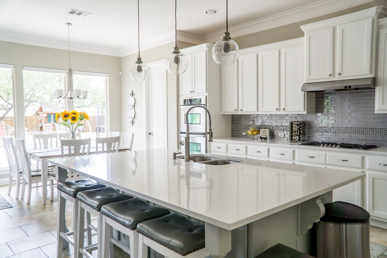 white kitchen island with pendant lights cabinet stools
