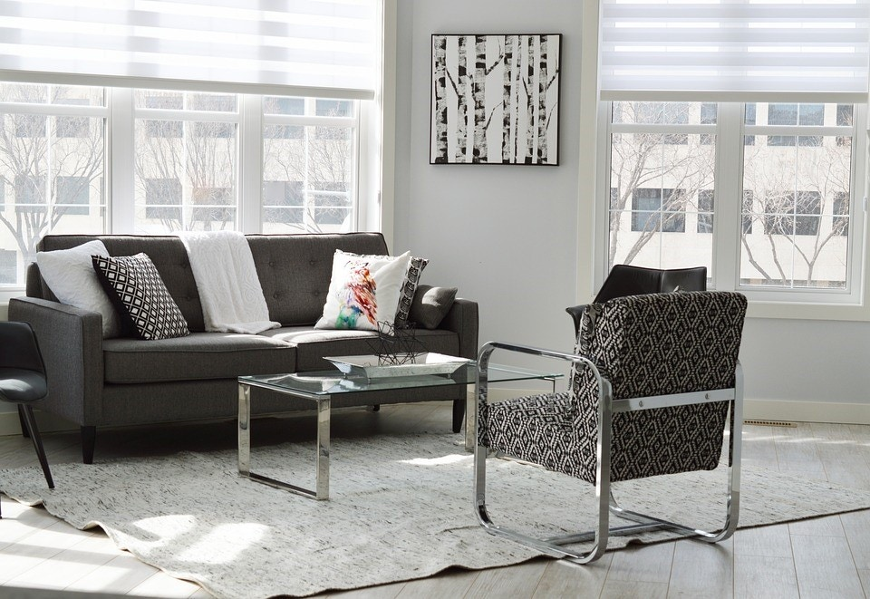 grey scale living room with couch chair table art windows