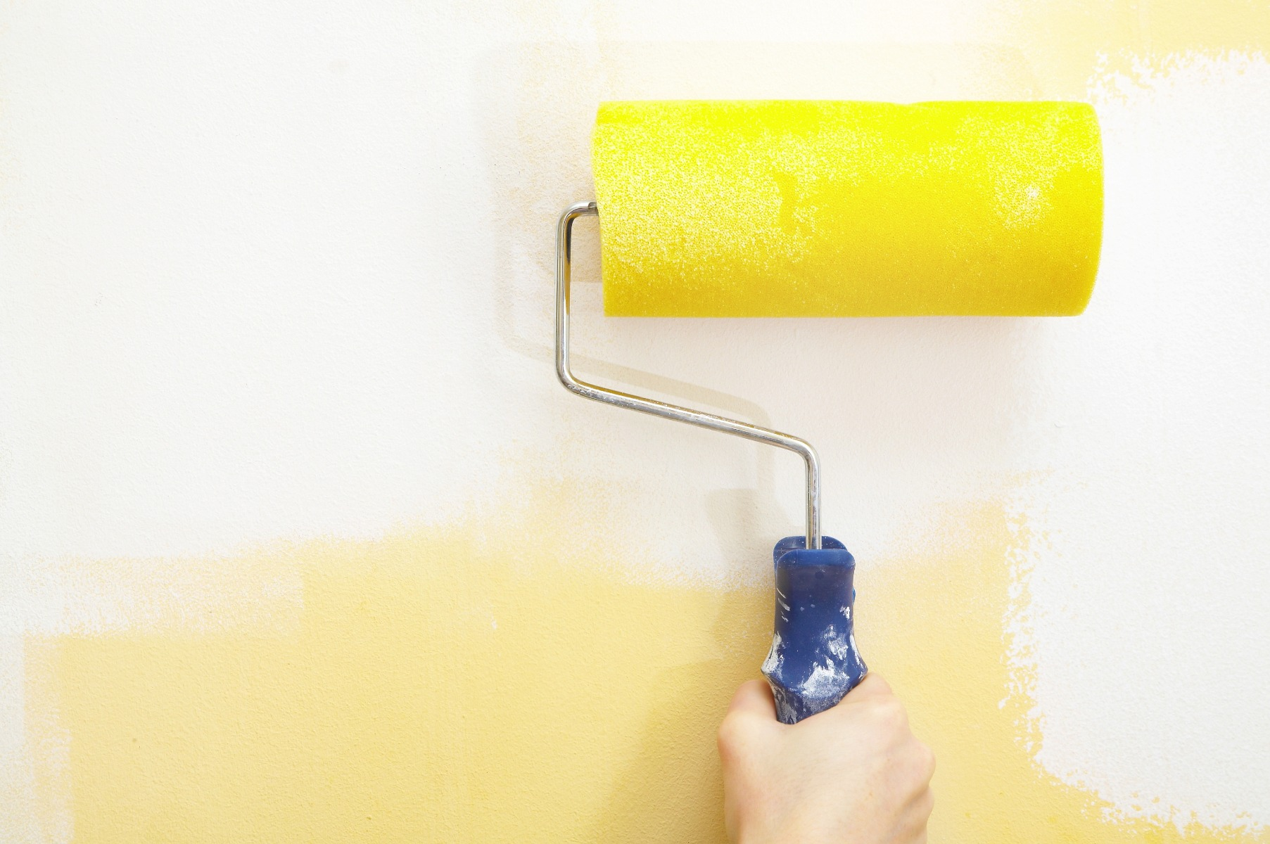 hand with yellow paint roller