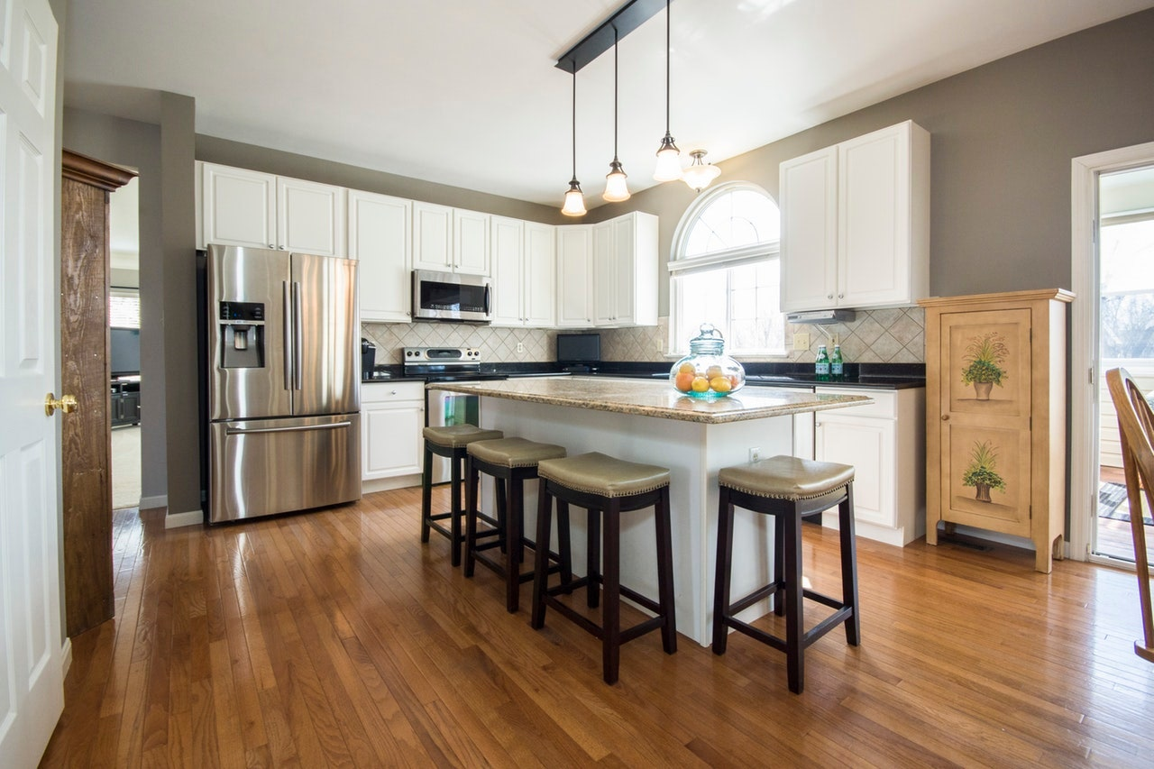 kitchen with grey walls, white cabinets, pendant lights, wood flooring